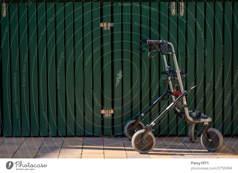 Lonely rollator in front of a green wooden wall Rollator Walking aid Senior citizen Exterior shot Old Mobility handicap aids mobile Healthy Wall (building)