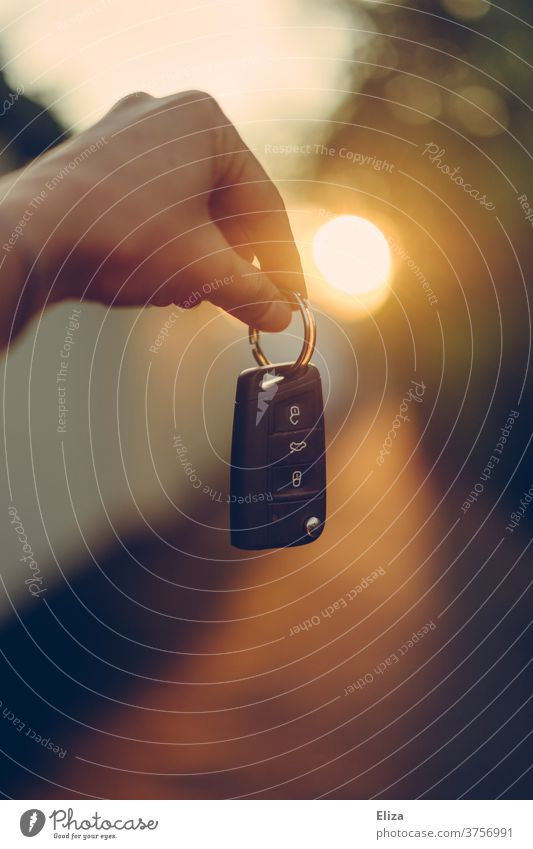 One hand holds a car key against the light car keys Back-light Driver's license car purchase by hand Street stop Shopping Key new car driving test insisted