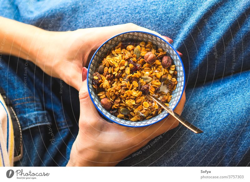 Girl eating granola yogurt bowl breakfast autumn healthy food cereal girl lifestyle jeans blue chestnut cranberries diet dried fall above fruit homemade honey
