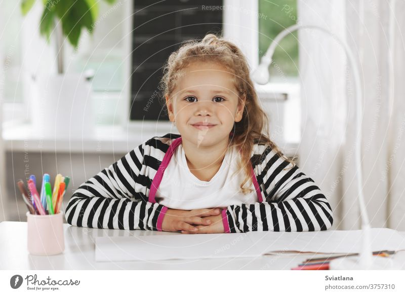 Portrait of a charming little girl sitting at a table. The girl is sitting at the table, on the table is a sketchbook, colored pencils. Homework, home training, social distance