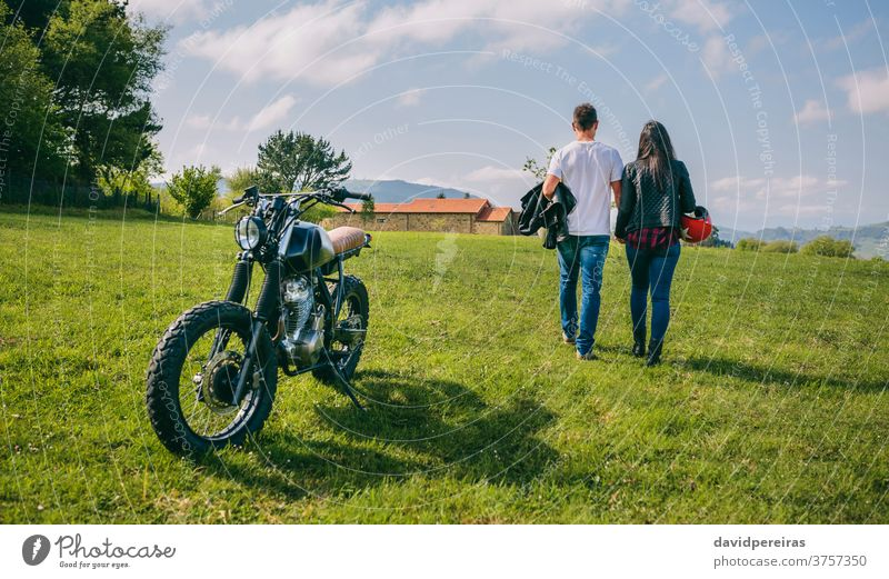 Couple walking on the field holding hands and motorbike unrecognizable backwards couple motorcycle parked trip man motorcycle helmet custom enamored built