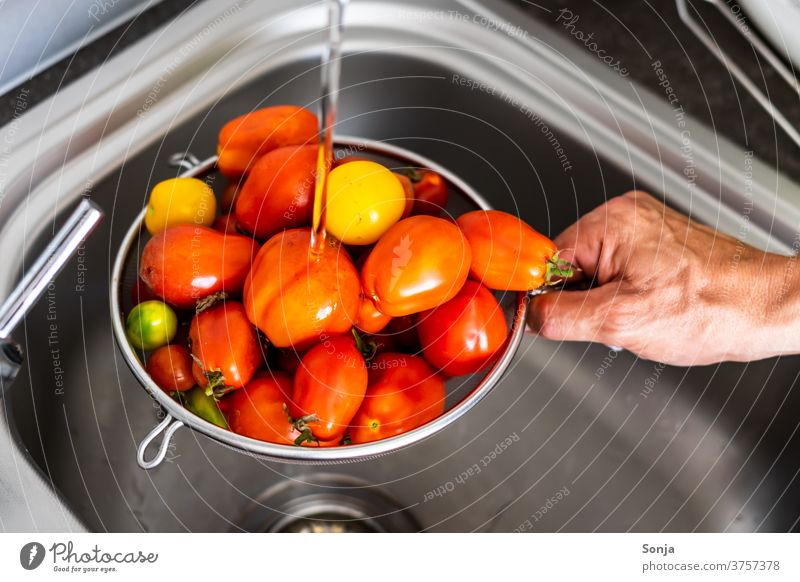 Man washes fresh raw tomatoes in a kitchen sieve over a sink Wash Kitchen sink Sieve by hand stop subsection Tap Water Cleaning cake Interior shot Nutrition