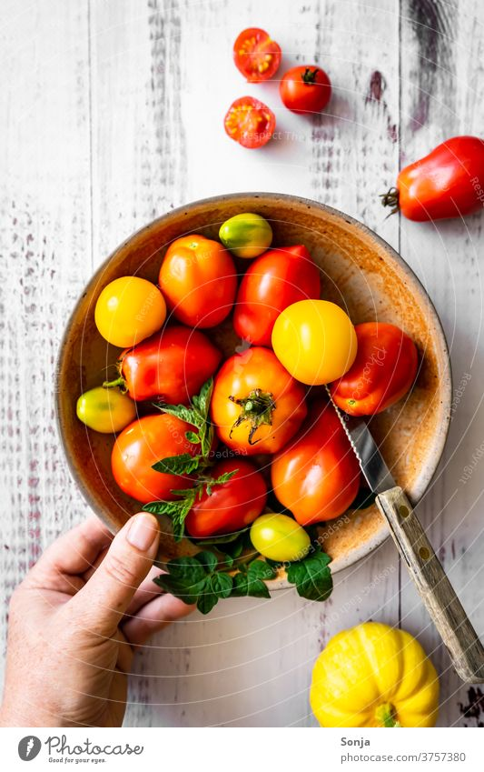 Hand with a plate of raw tomatoes on a wooden table. Top view, healthy diet. Red Raw Plate Wooden table by hand stop Knives Vegetable Colour photo Nutrition