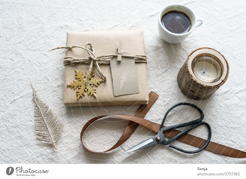 Christmas wrapped present with scissors and a cup of coffee on a beige background Gift Claw Packaged Coffee Cup Band retro style Beige Linen cloth Close-up