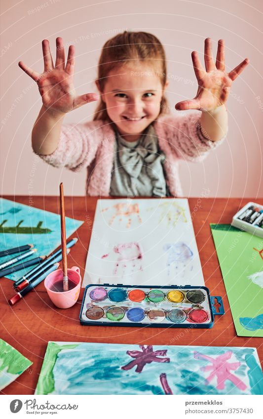 Little girl preschooler showing painted colourful hands child painting dye education colorful art home paper childhood creation craft table creativity kid