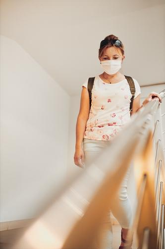 Woman going downstairs wearing face mask to cover mouth and nose during pandemic coronavirus outbreak woman pharmacy covid-19 female care indoor person protect