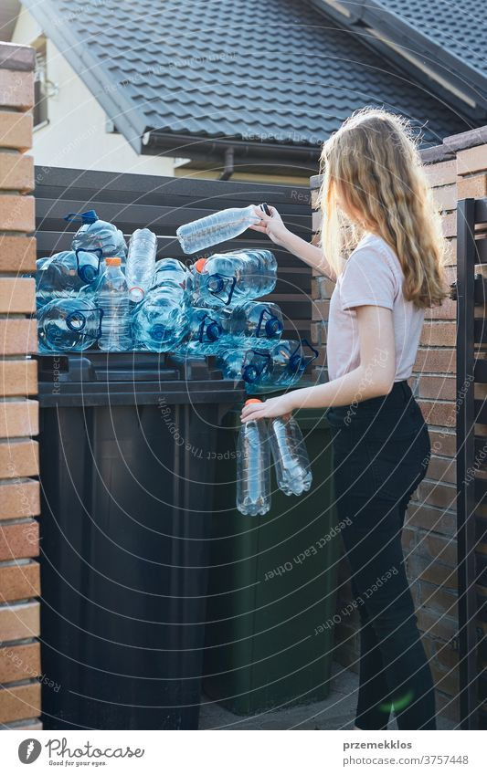 Young woman throwing out empty used plastic water bottles into trash bin blue collect collecting container crushed disposal ecology environment female garbage
