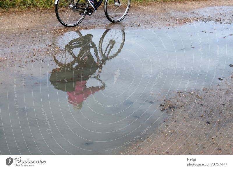 Cyclist mirrored in a large puddle on a dirt road | dynamic Bicycle cyclist reflection Puddle Nature Environment off the beaten track Exterior shot Reflection