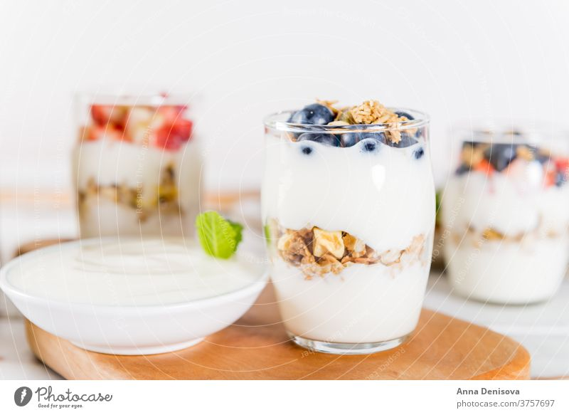 Little Jars with layered dessert from natural yogurt, granola an breakfast healthy muesli food fruit meal white sweet fresh bowl organic greek wooden cereal