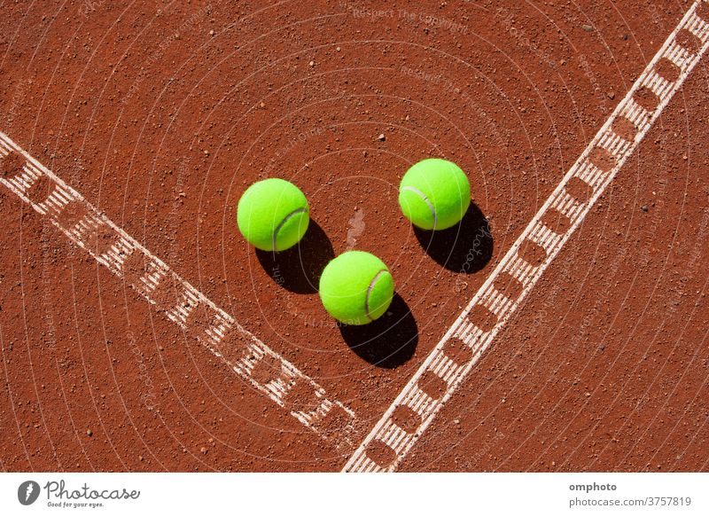 Three tennis balls in the corner of a clay field court line game red ground orange sport activity white outdoor set competition play exercise equipment