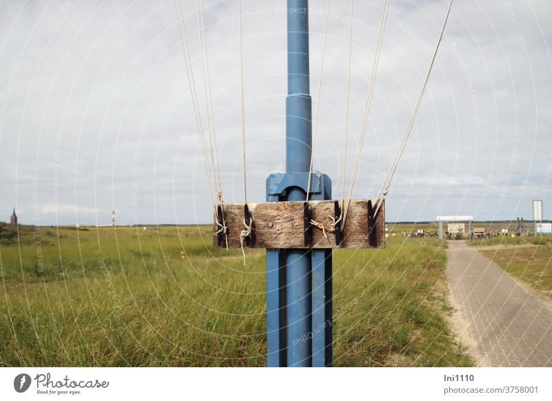 Partial view of flagpole with rope attachment North Sea Island Wangerooge port area Flagpole Blue Grass Mounting option Wood ropes Knot Tighten Nostalgia