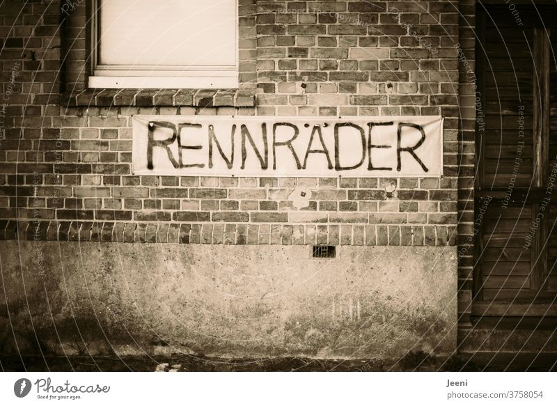 """Masonry wall in a city with the banner """"RENNRÄDER"""" (racing bikes) Wall (building) Stone stonewalled Wall (barrier) Racing bikes Racing cycle sign Wheel brick"""