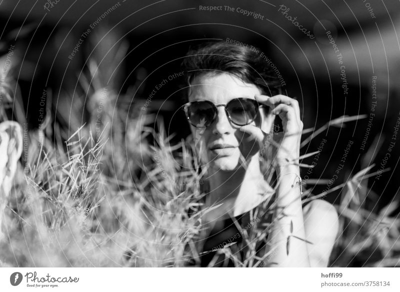 surprised, the woman looks into the camera and grabs her sunglasses Meditative portraite Face of a woman Adults 18 - 30 years Feminine Women's eyes already