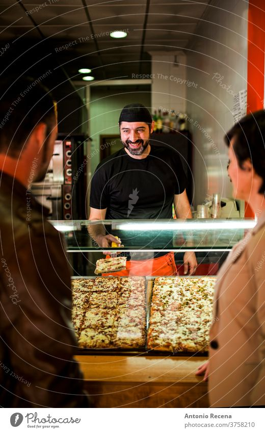 Young couple buying pizza at night restaurant fast food bar. man turkish ale adult person people attractive men male bearded seller store junk food business