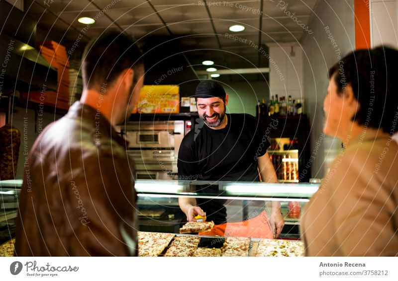 Couple buying and choosing pizza at street outdoors restaurant. man turkish adult person people lifestyle attractive men male bearded seller store junk food