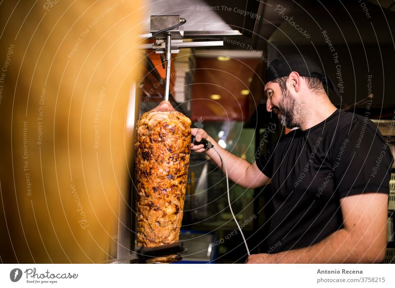 Bearded man preparing kebab meat in pizza bar. turkish adult person people lifestyle attractive men male bearded store junk food business portion night smile