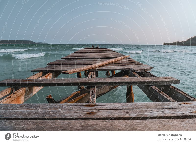 Cinematic summer scenery of a broken wooden pier in against the vast blue sea at Sok San Beach Koh Rong Island in Cambodia showing concept of supporting mental health, social isolation and social distancing during the covid-19 pandemic