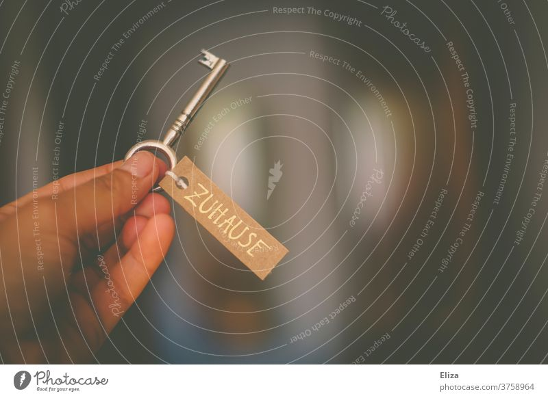 """One hand holds a key with a label on it with the words """"home"""". at home dwell Key House key Home House (Residential Structure) rent Shopping living space sign"""