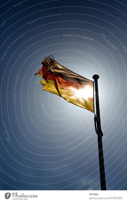 waving, shining German flag with shining through sun shines in the back light before cloudless sky. Germany flag, black-red gold Sun German Flag Wind Blow