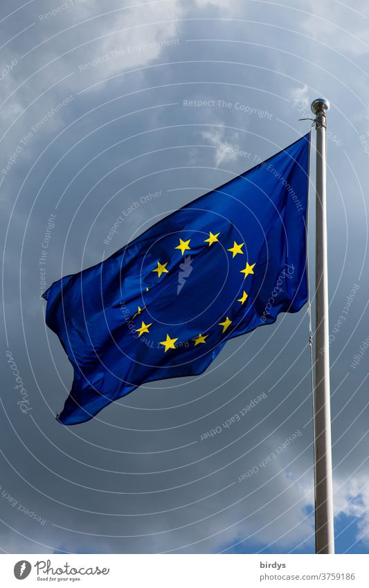 European flag , Flag of the European Union waving in the wind . Thunderclouds in the background Wind waving flag Blue yellow stars identification Pride positive