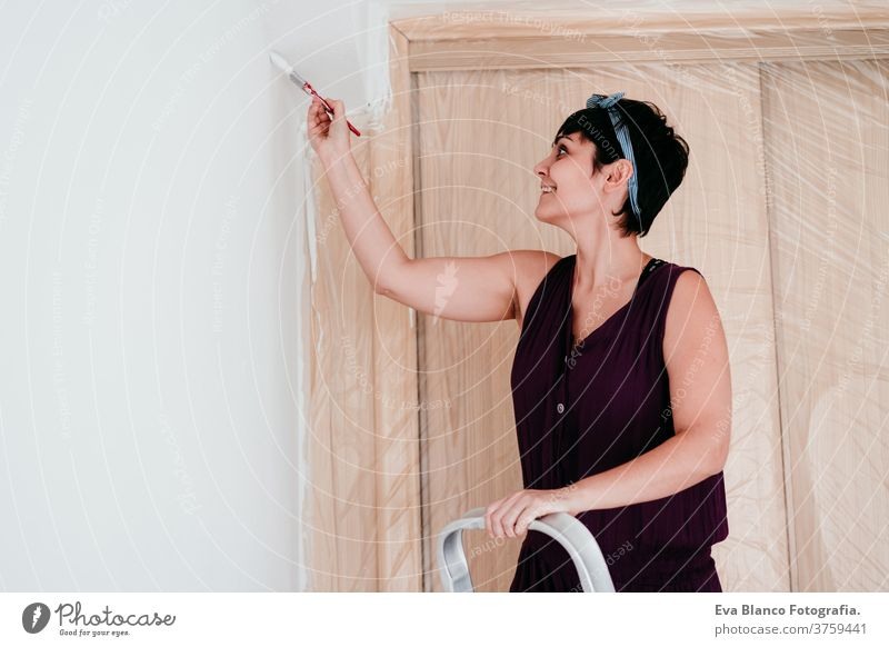 happy caucasian woman painting the room walls with white color. Do it yourself and new home concept house brush young new house painter bricolage america solo