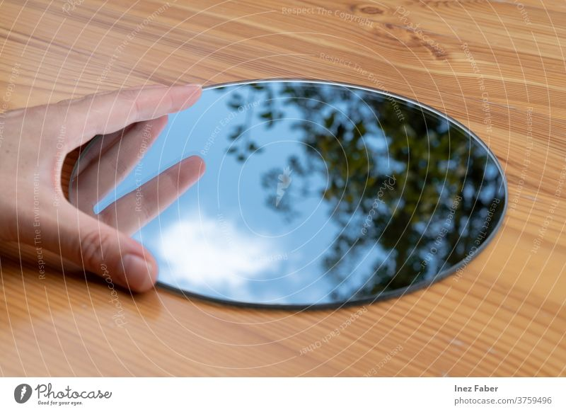 Hand held round mirror on a table, reflection of a tree, clouds and blue sky calm catch the sky cloud reflection tree reflection hand held mirror wooden table