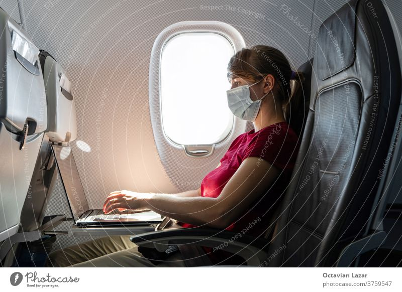 Caucasian young woman wearing pandemic medical face mask working on her laptop on an airplane seat during flight businesswoman distance social passenger using
