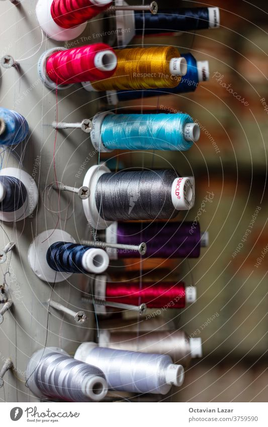 Multi color small spools of sewing thread stacks on large cylinder display blue green red pink palette turquoise orange yarn stitch garment stitching colour
