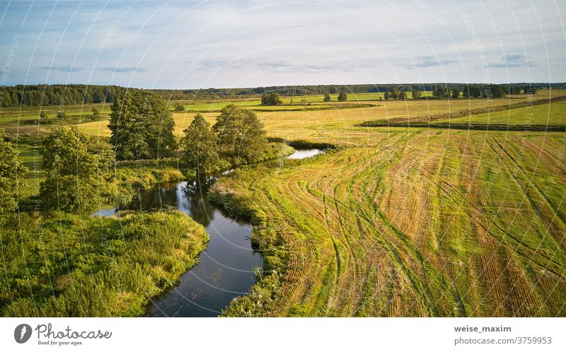 Autumn landscape in evening sunlight from above. Agriculture fields after harvest tree autumn fall river sunny water September nature reflection blue aerial