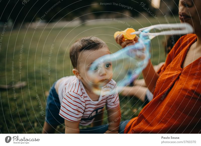Mother and child playing with soap bubbles Soap bubble Playing Leisure and hobbies motherhood Toddler outdoors Caucasian Authentic Lifestyle Colour photo Happy