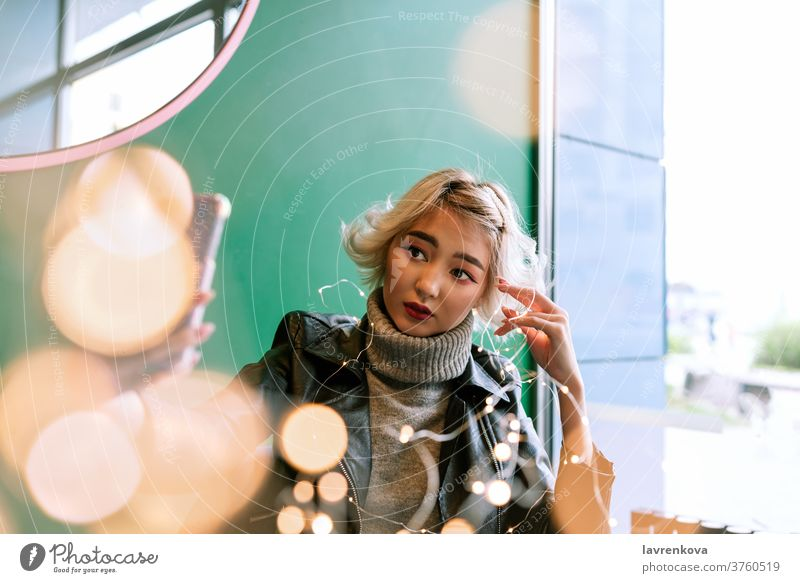Young asian female with blond hair making selfie with fairy lights winter autumn xmas seasonal adult bokeh cafe christmas lights coffee shop fashion girl