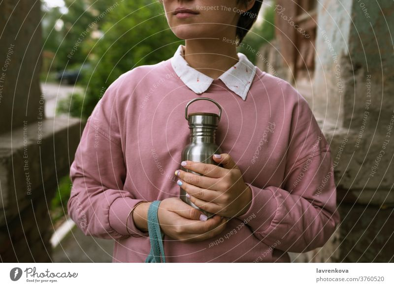 Female in pink sweatshirt holding sustainable metal eco bottle with her hands outdoors, selective focus closeup fingers female woman girl zero waste water
