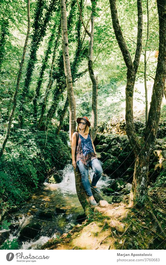 Young woman by the tree in the forest adult adventure adventurer beautiful casual caucasian enjoying environment explore female free freedom fresh green