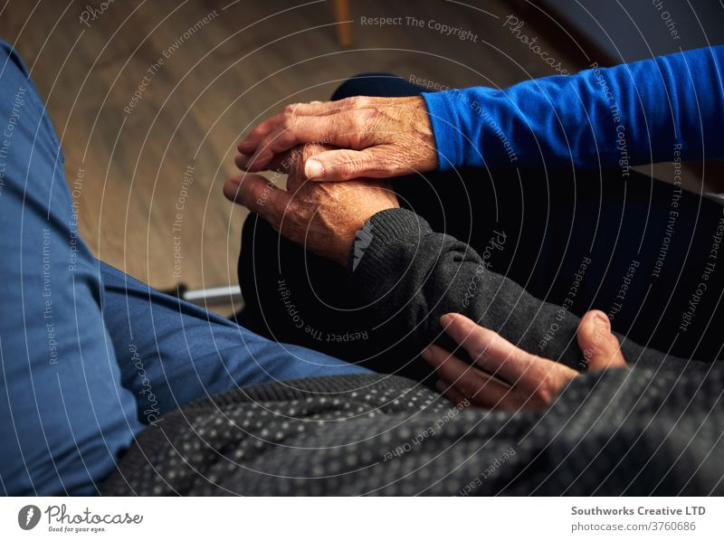 Older couple holding hands on the sofa Senior citizen care Participation Love Man Wrinkled Resting Relaxation Home Bond people Lifestyle indoors more adult