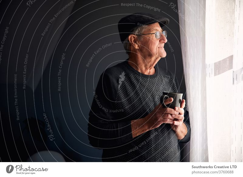 Senior man smiling out of window senior male hat glasses home happy looking copy space retired coffee mug cup waiting mature pensioner indoors lonely eyeglasses