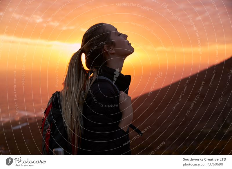 Profile view of young woman with eyes closed on top of mountain at sunset outdoors adventure nature person travel one summer leisure activity backpack
