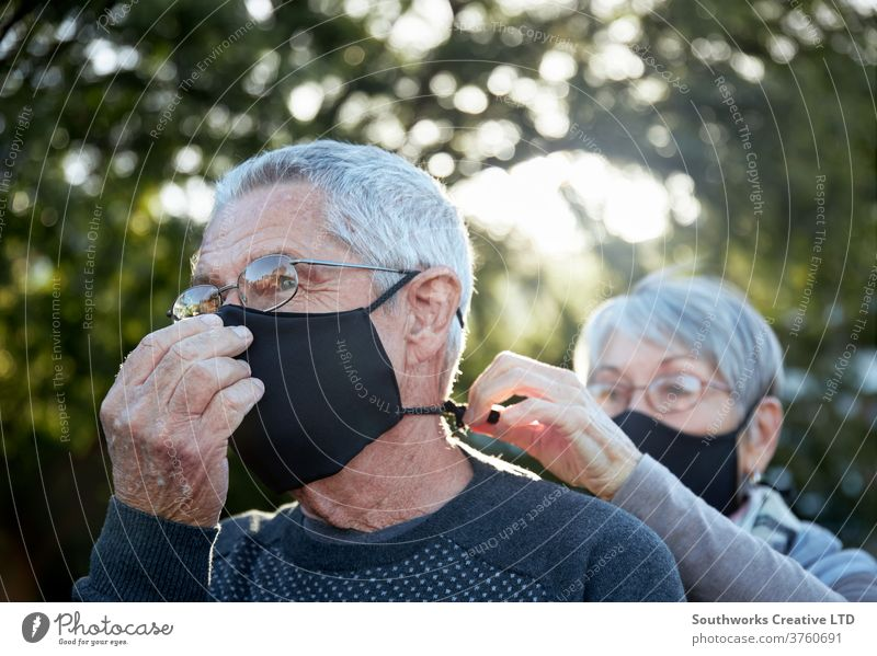 Active senior couple on outdoor walk wearing face masks elderly covering mature happy love outdoors retired active caucasian copy space female man old partner