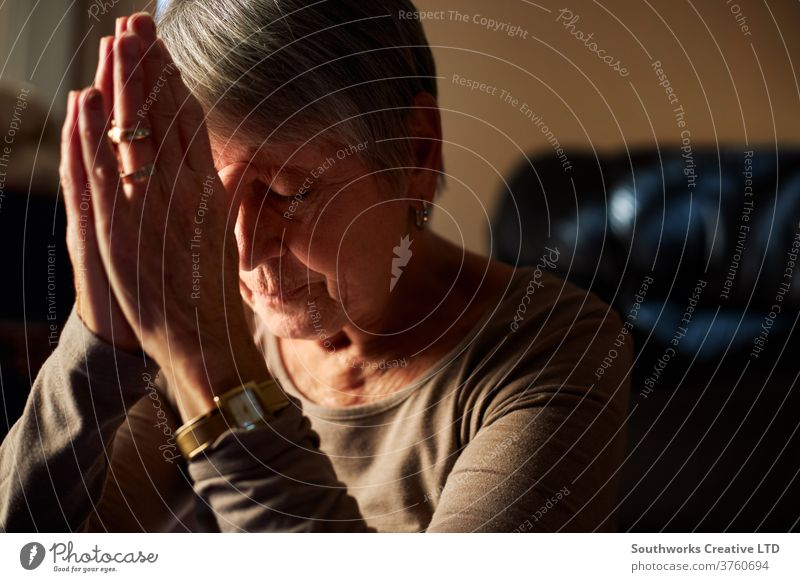 Senior woman praying at home female house sunlight aged calm indoors mature person adult care elderly senior old oap faith prayer hands pensioner morning living