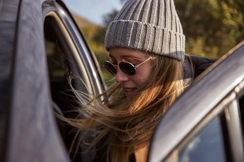 Young woman packing car for road trip adventure outdoors person activity leisure backpacker traveling female explorer young adult active hike hiking sunny hat