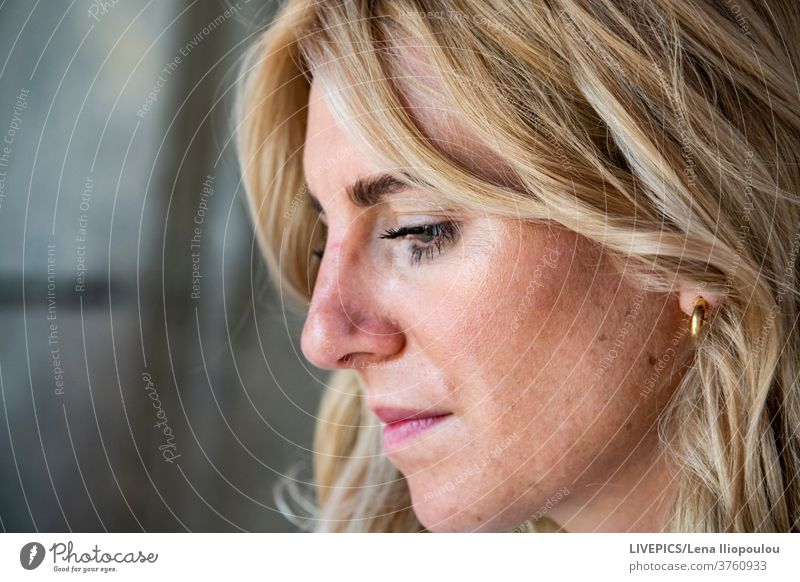 Side portrait of a young lady woman dame side view profil blond looking away profile serious one person outdoors people face hair head eyes close-up copy space