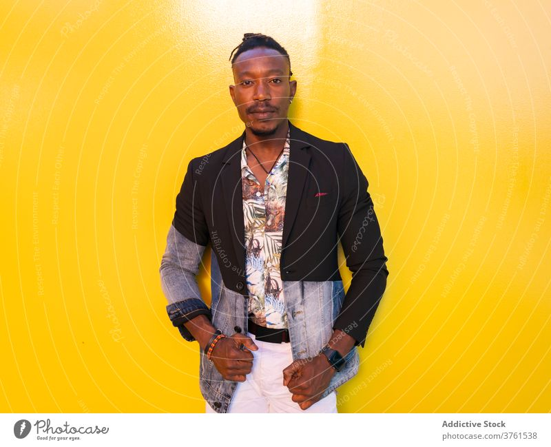 Confident ethnic man in stylish wear in city model fancy style apparel vivid yellow wall trendy male black african american fashion outfit urban confident
