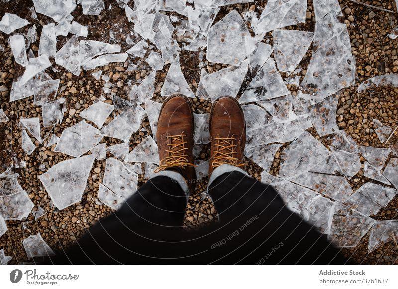 Crop traveler standing on ground with ice lake tourist winter trekking boot season vacation frozen scottish highlands scotland uk united kingdom cold adventure