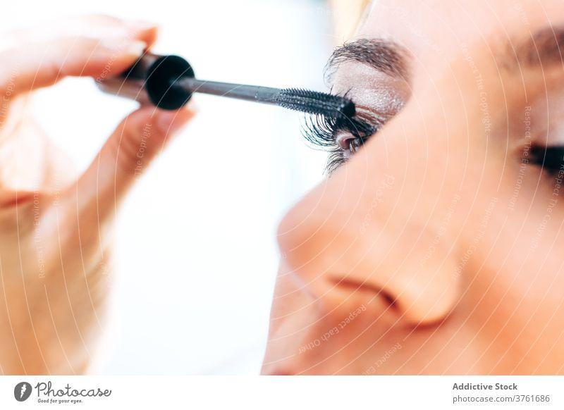 Crop visagiste applying mascara on model makeup artist visage professional beauty product procedure brush client prepare salon customer beautician vogue work