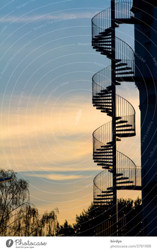 spiral staircase at a building in front of a beautiful evening sky. spiral staircase Winding staircase External Staircase spirally Evening Spiral Handrail