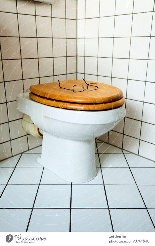Brille auf der Klobrille bad dusche hygiene klo klobecken klobrille optiker sanitär sehhilfe toilette toilettenbecken wc zu zugeklappt kacheln fliesen