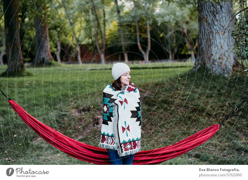young woman covering with blanket standing next to hammock. autumn season. camping concept cold outdoors nature sunset orange park caucasian preparing relax