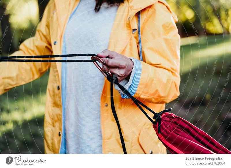 unrecognizable woman wearing yellow raincoat preparing hammock to relax. Camping outdoors. autumn season sunset orange park caucasian happy campground morning