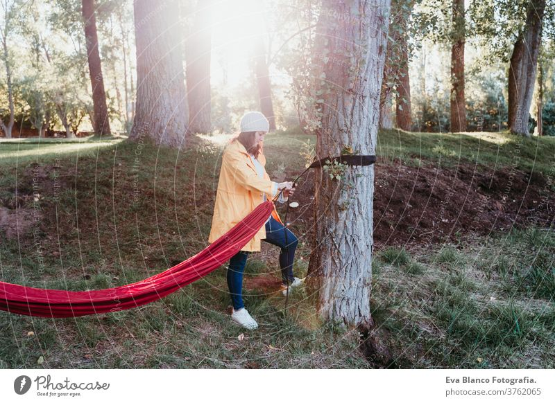 young woman wearing yellow raincoat preparing hammock to relax. Camping outdoors. autumn season sunset orange park caucasian happy campground morning light