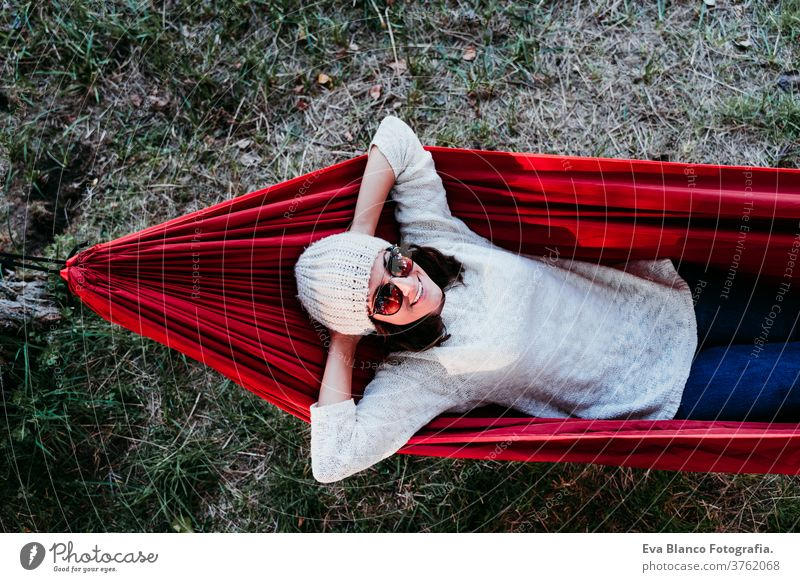 young woman relaxing in orange hammock. Camping outdoors. autumn season at sunset lying nature park caucasian preparing happy campground morning light