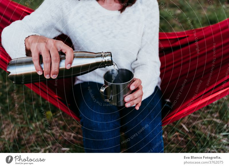 young woman holding thermos, pouring water into metallic mug, relaxing in hammock at sunset. autumn season unrecognizable feet lying outdoors nature orange park